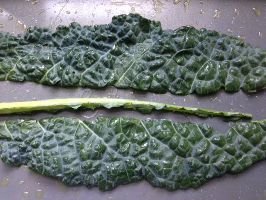De-veining kale by taking stem out of the middle.