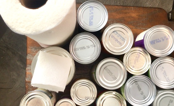 paper towels to clean cans for a clean pantry