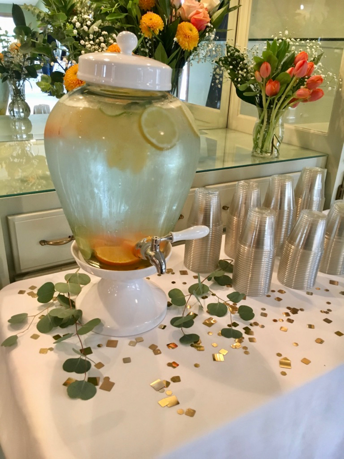 water dispenser with fruited water on a table with confetti