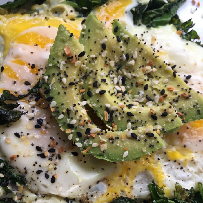 egg and spinach topped with avocado slices
