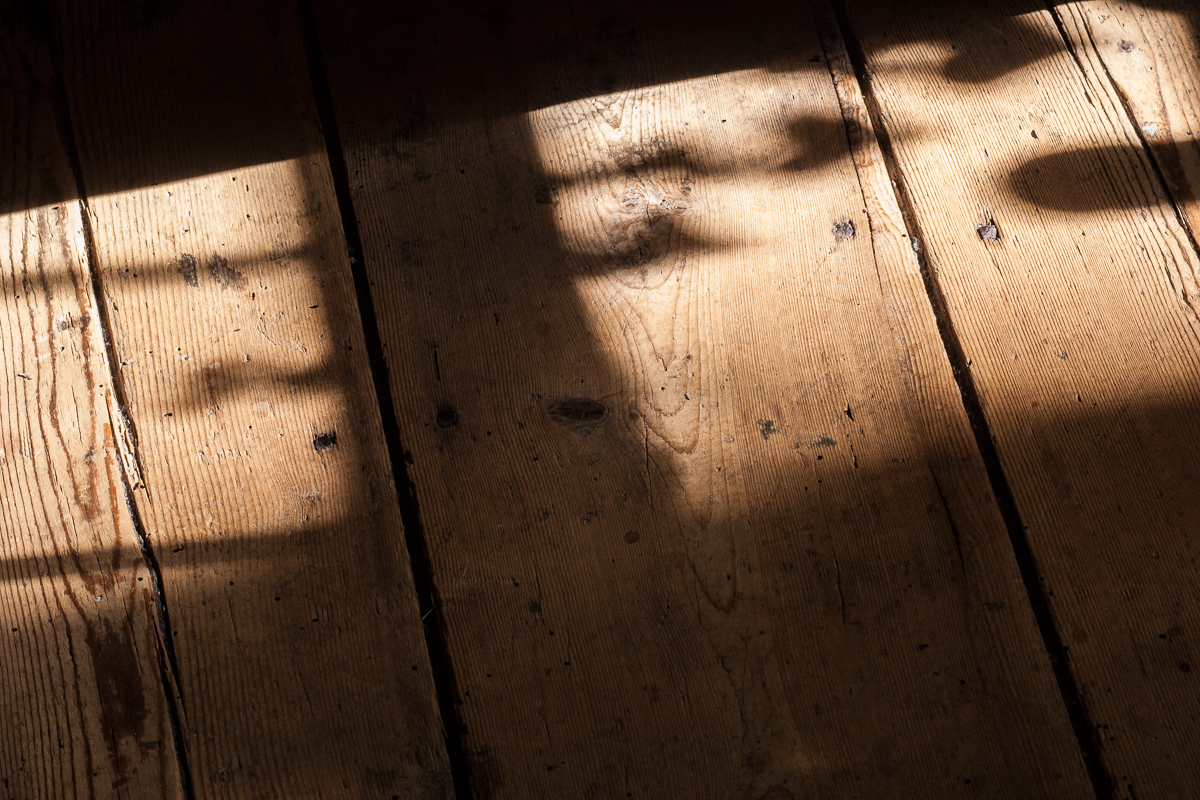 Photographic image of an old rustic and unfinished floor with shadows falling across the old, scarred wood.