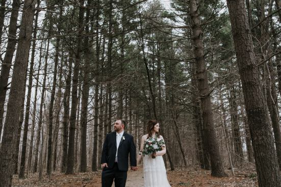 wedding couple looking in opposite directions while holding hands in a forest