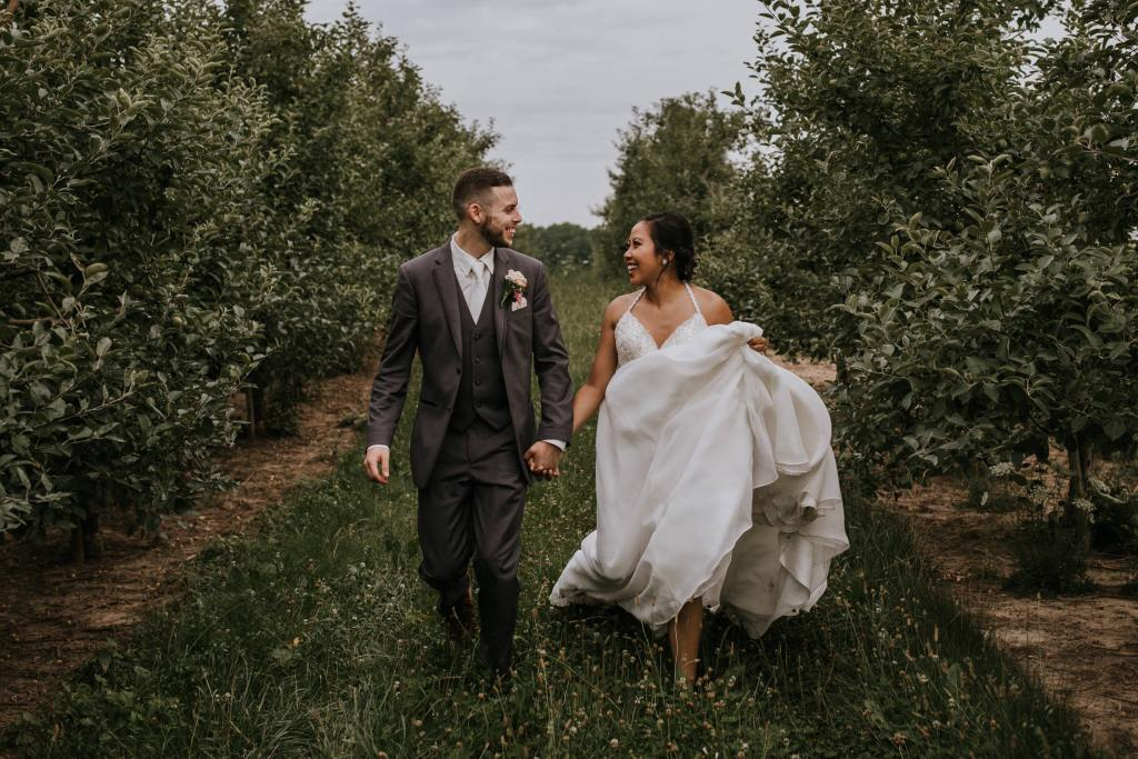 Bride and groom running through an apple orchard