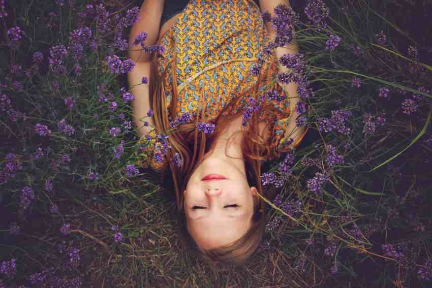 Beautiful girl lying in a field of lavender