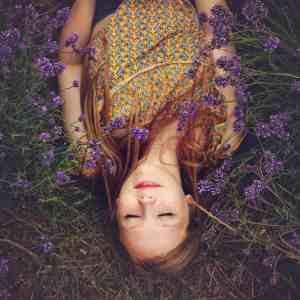 Beautiful girl lying in a field of lavender