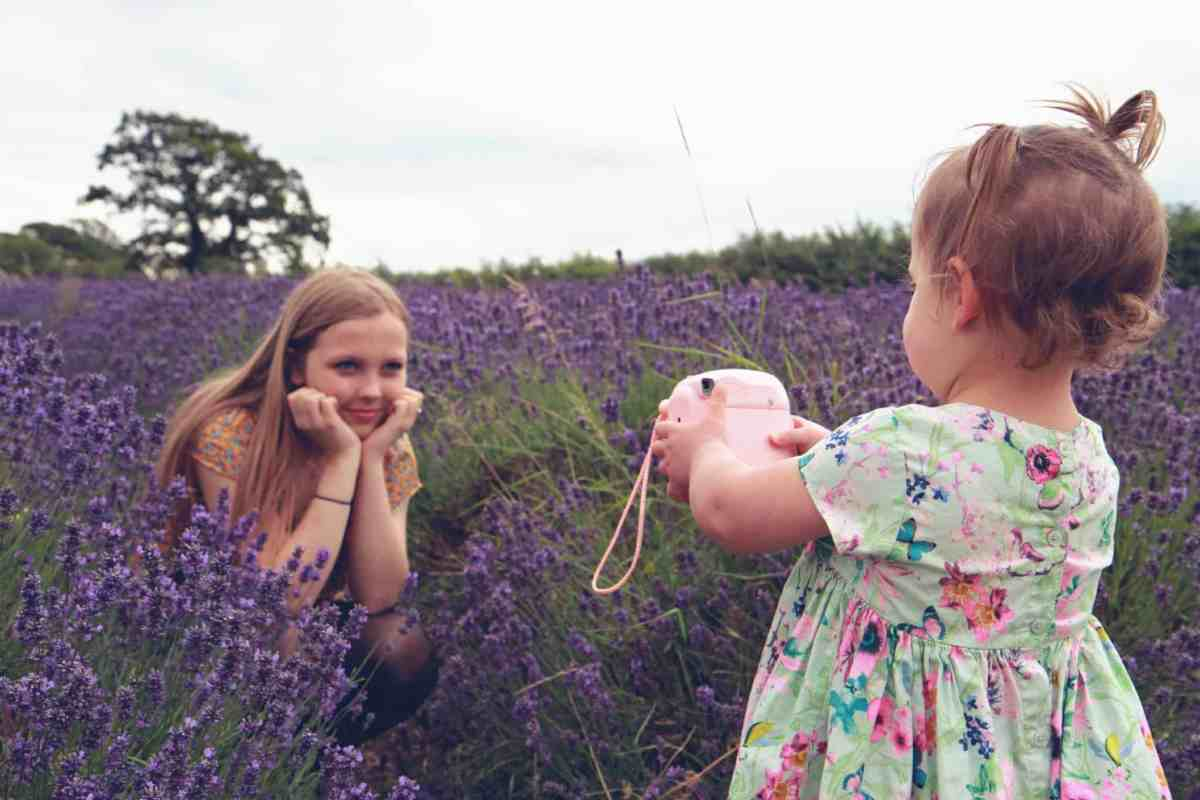two sisters playing with a polaroid camera in the middle of a lavender field