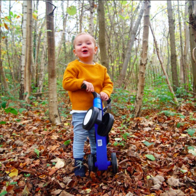 little boy testing out his toddle bike in the woods