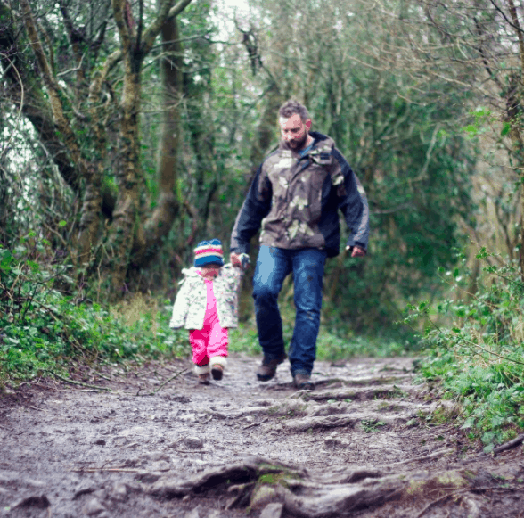 Daddy and daughter walking through the woods at Eagle's Nest