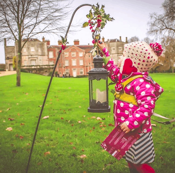 Little girl reaching up to a Christmas lantern in the grounds of a manor house