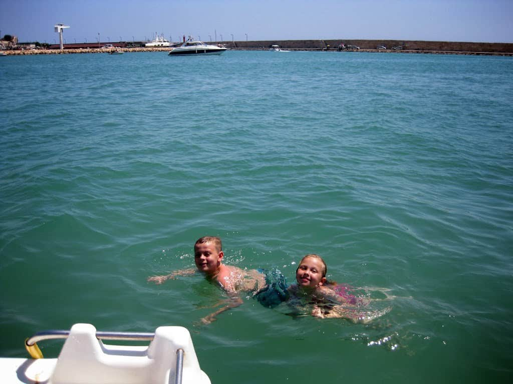 Lewis and Holly swimming beside a pedalo