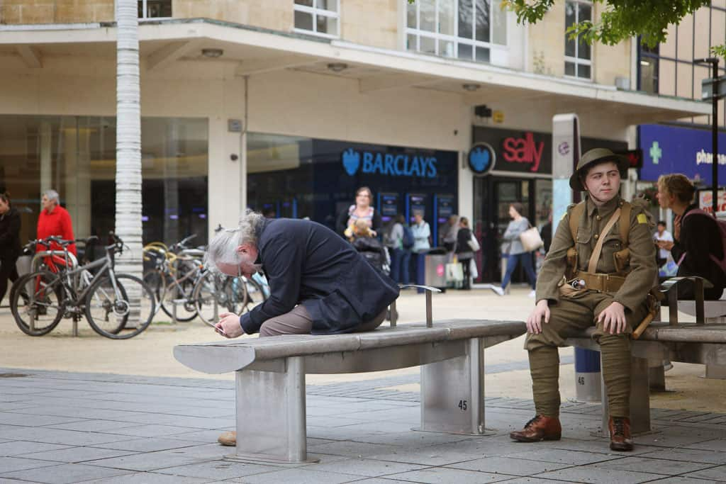 A spectator having a moment of prayer watching soldiers dressed in WW1 uniform walk the streets of Bristol