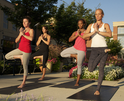 Three white women and one black woman doing yoga standing in tree pose.