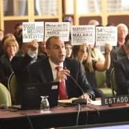 """El representante del Estado Venezolano, Larry Devoe, responde a miembros de la Comisión Interamericana de Derechos Humanos (CIDH), mientras asistentes a la audiencia pública """"Derecho a la alimentación y a la salud de Venezuela"""", protestan contra el Gobierno de Caracas hoy, 27 de febrero de 2018, en Bogotá (Colombia)/ Foto: EFE"""