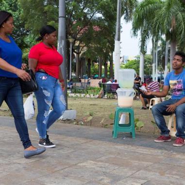 El venezolano Jonathan Tilano (d), de 23 años, vende jugos en una plaza el pasado viernes, 27 de julio de 2018, en Santo Domingo (República Dominicana)/ Foto: EFE