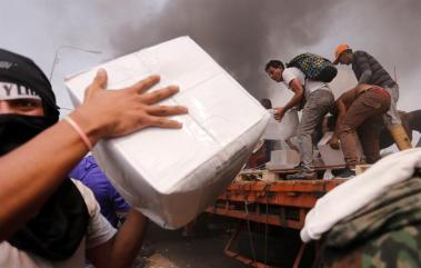 Jovenes se dispusieron a bajar las cajas/Foto: EFE