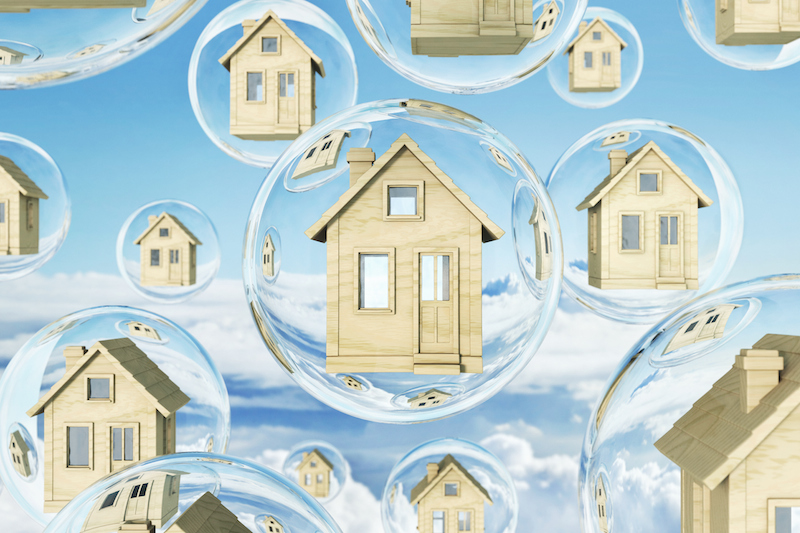 Toy wooden miniature houses floating in bubbles