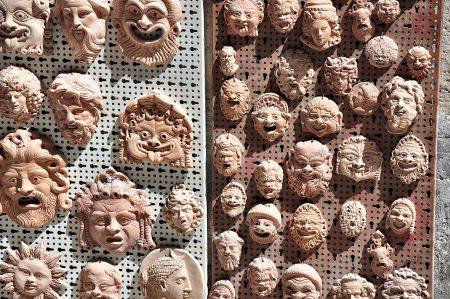 Selbst winzige Terracottamasken bei einem sizilianischen Andenkenladen verweisen auf die große griechisch-antike Vergangenheit von Syrakus. (Foto: Martin Dühning)