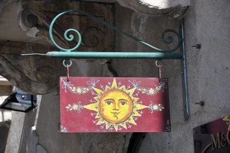 Ladenschild mit Sonne - neben der Triskele mit Medusa ein Symbol für Sizilien (Foto: Martin Dühning)