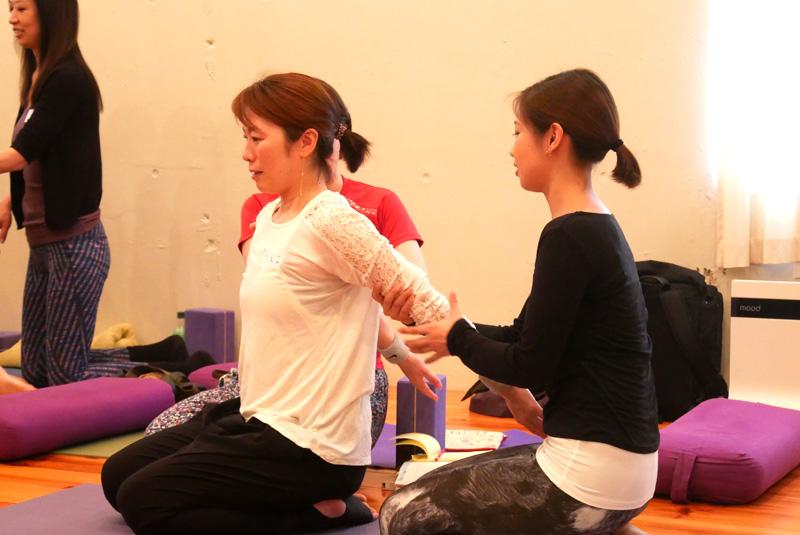 女性二人。一人が腕を背中のほうへ伸ばしている。もう一人が腕に手を添えてアジャストしている