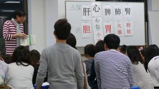 経絡の説明をしているヨガ指導者と耳を傾ける大勢の生徒