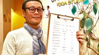 ヨガ解剖学講師内田かつのり先生が「怪我をしない、させない」の資料として使われるヨガクラスの参加問診票をもって微笑んでいる。