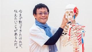 ヨガ解剖学講師内田かつのり先生が全身骨模型の頭部を指さして笑顔でほほえんでいるところ