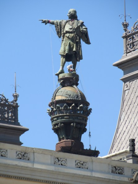 Statue of Columbus over rooftop