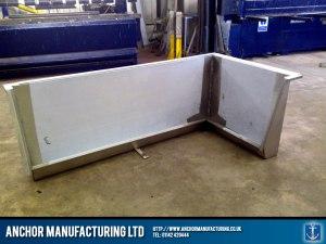 Corner urinal trough design in stainless steel.