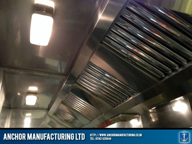 Industrial sized kitchen canopy with bulkhead lighting.