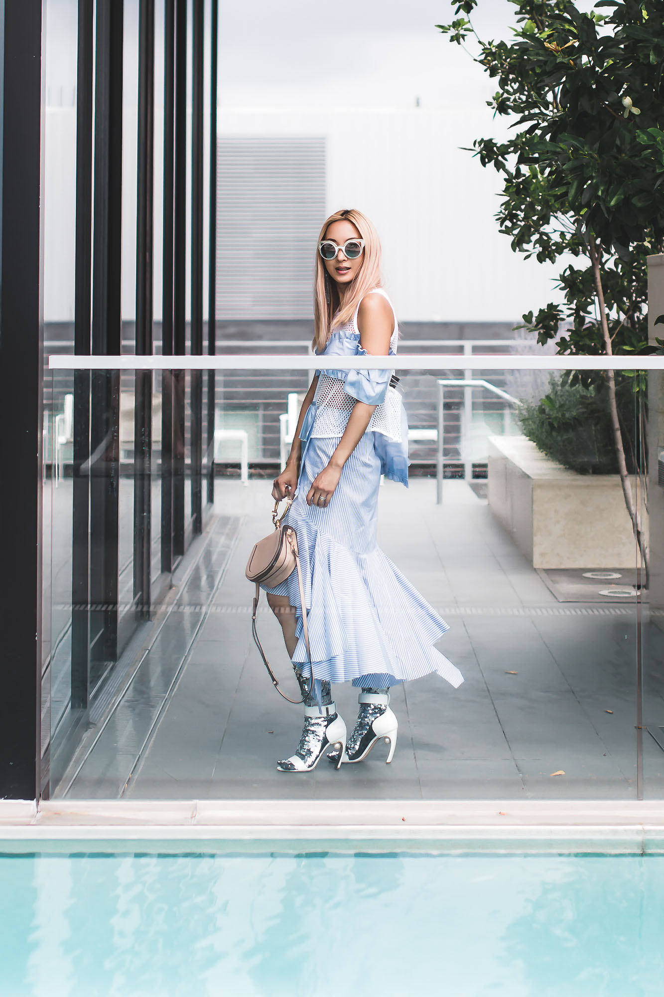 Anchyi Adorned Fashion blogger in Sandyn Liang ruffle open knit top, Off-White deconstructed shirting skirt, sequin socks and Chloe nile bracelet bag.