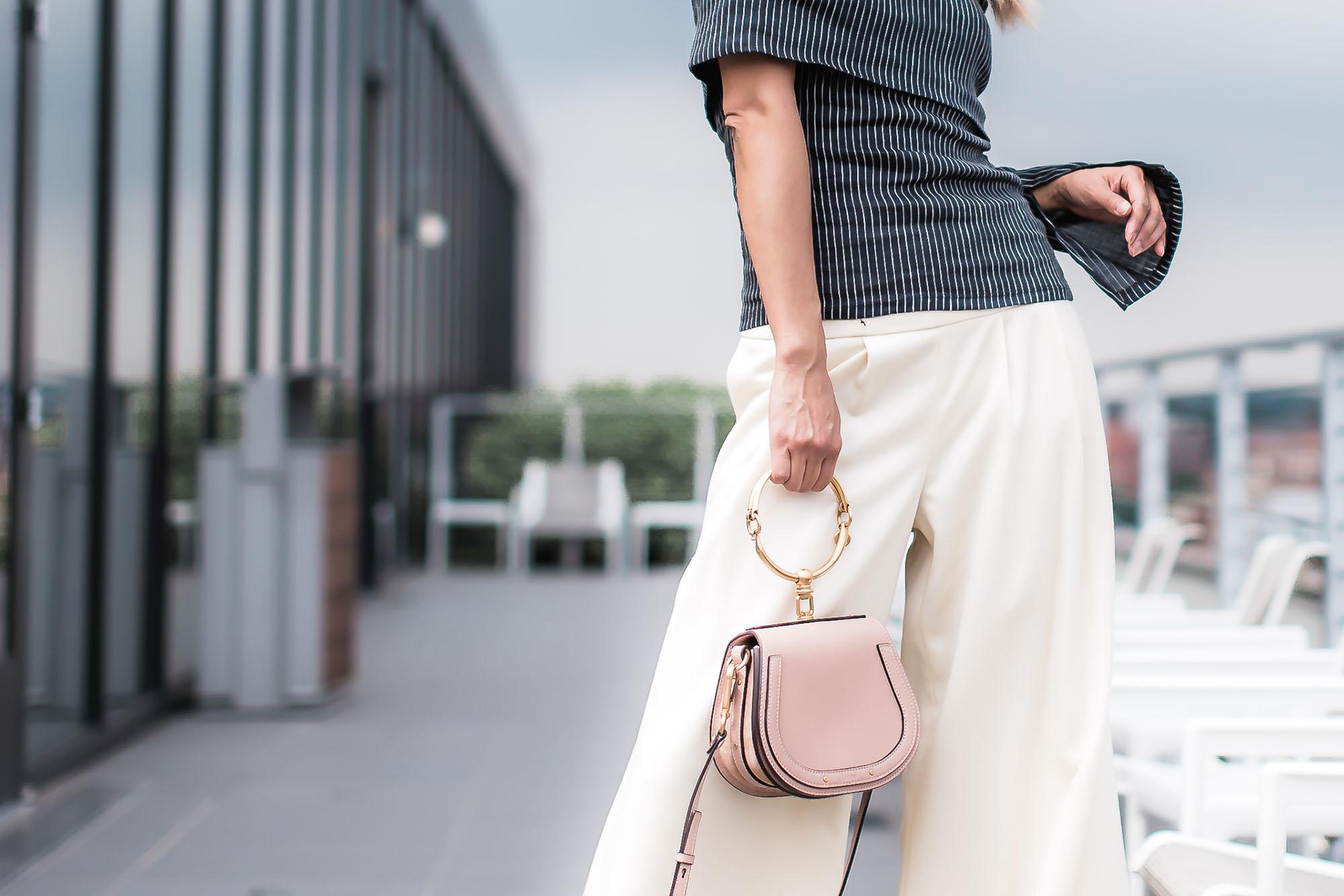 Anchyi Adorned fashion blogger in Beaufille off shoulder top, Chanel white wide leg pants, and Chloe Nile bracelet bag