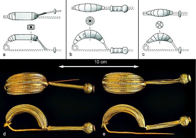 Las tres fíbulas de ámbar (a-c) y dos fíbulas de oro tipo navicella (d-e) se encontraron en puntos diversos de la parte superior del enterramiento principal. (Fotocomposición: Antiquity/Cambridge Core)