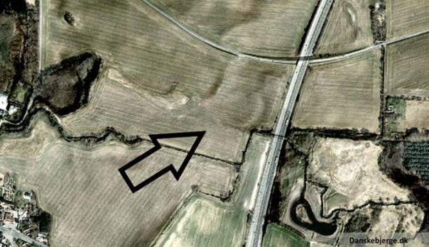 Fotografía aérea de Vallø Borgring. Versión modificada de una fotografía de satélite en la que se han sombreado los relieves. La flecha señala en lugar en el que se observa una forma circular, emplazamiento de la antigua fortificación. (Danskebjerge/CC BY SA 3.0)