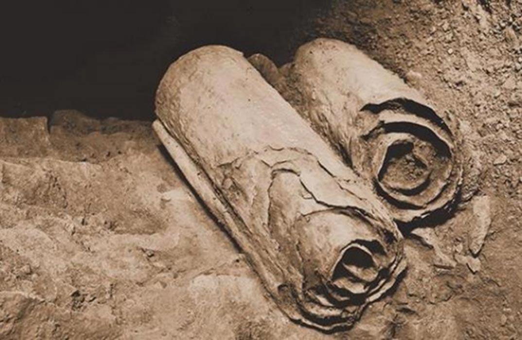 Dos manuscritos del Mar Muerto en su ubicación original de las cuevas de Qumrán poco antes de ser recuperados por los arqueólogos para su conservación y estudio. (Public Domain)