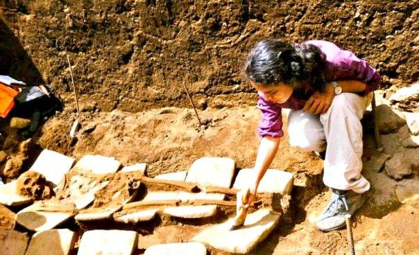 Arqueóloga trabajando sobre algunos de los restos óseos hallados recientemente en Nicaragua. En esta fotografía se aprecia claramente uno de los lechos de metates sobre los que fueron depositados algunos de los cadáveres. (Fotografía: Canal 4)