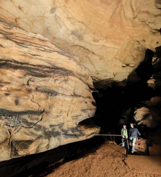Beau Duke Carroll y Julie Reed en la cueva Manitou, con un silabario Cherokee visible en el techo. (A. Cressler / Uso Justo)