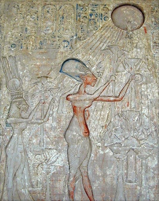 Faraón Akenatón (centro) y su familia adorando a Atón, con los rayos característicos visto que emana del disco solar.