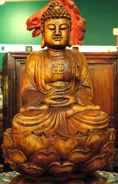 Wooden Buddha statue with gamadian (swastika). (CC BY 2.0)
