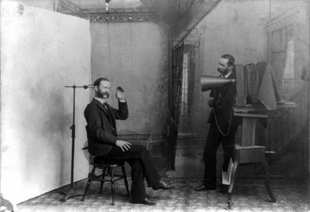 Una fotografia composita del 1893 che mostra un interno di uno studio fotografico. Un uomo è seduto su uno sgabello vicino a un morsetto regolabile per tenere la testa ferma durante una lunga esposizione verticale. Il secondo uomo, in piedi accanto a una grande telecamera, sembra la persona fotografata. (Dominio pubblico)