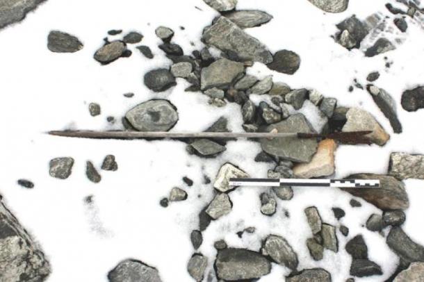 Una freccia dell'800 dC trovata sul terreno in Norvegia, in parte coperta di neve. (Espen Finstad, I segreti del ghiaccio, Consiglio della contea di Oppland)