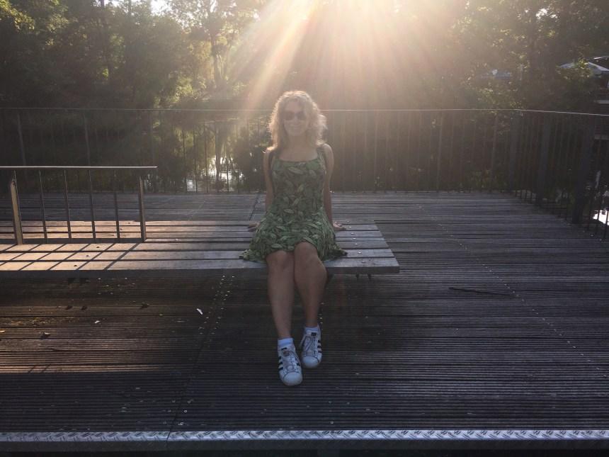 Lizzi sitzt auf einer Bank auf einem Holzsteg.