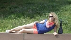 Lizzi liegt in Shorts auf einer Mauer.