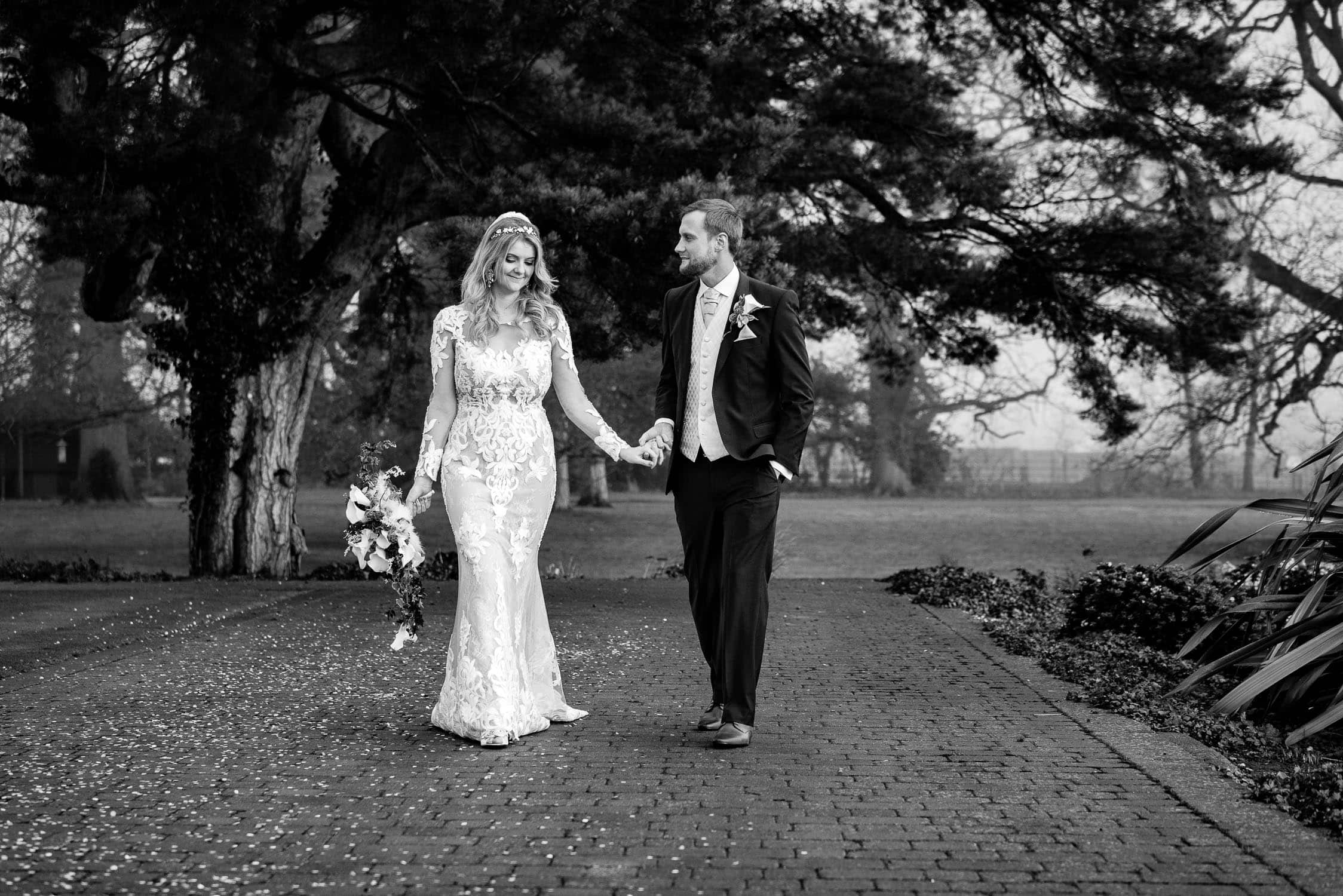 bride and groom walking in the grounds of Rockliffe Hall after their wedding ceremony