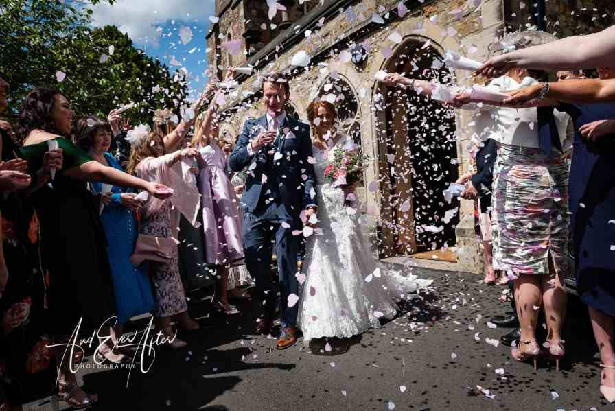 Wedding day confetti photograph with couple outside church