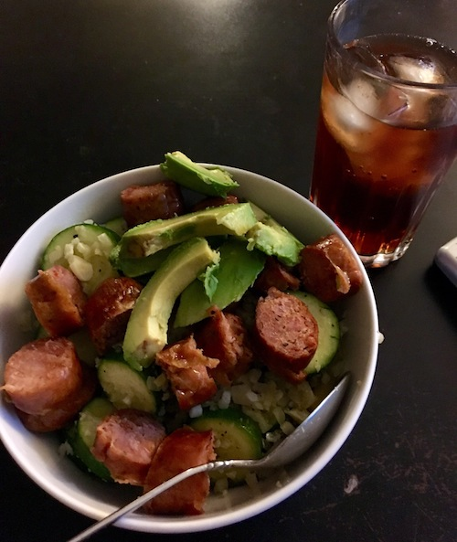 Zucchini cauliflower rice stir fry with red peppers, onions, and garlic with sausage and sliced avocado on top.