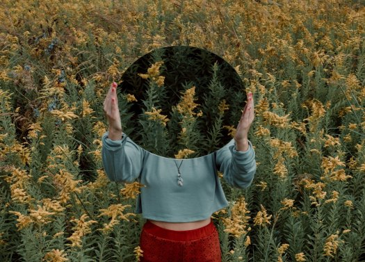 standing woman holding a mirror surrounded by goldenrod