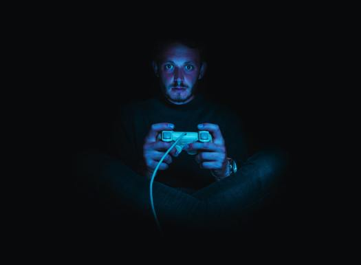 A man sits in the dark holding a video game controller - horror video games