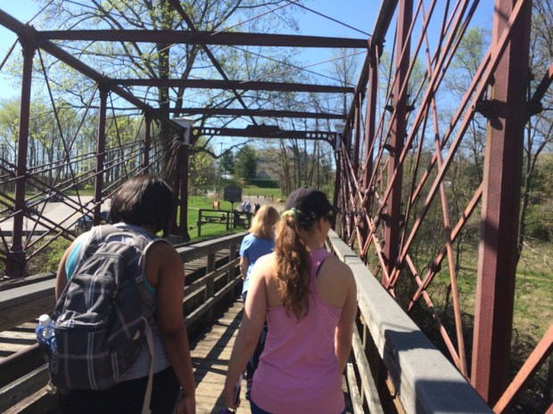 Hikers on the Bollman Truss railroad bridge adjacent to the mill