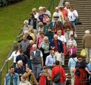 Группа иностранных туристов в наушниках-переводчиках. Нижний парк Петергофа.