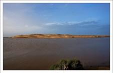 Большая песчаная дюна между лагуной и океаном.